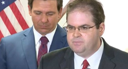 Robert J. Luck in a screen capture from the press conference where Governor Ron DeSantis (rear) named him as the 88th Justice on the Florida Supreme Court.